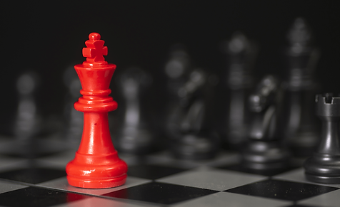 A chessboard with one red piece standing out in front of all black pieces