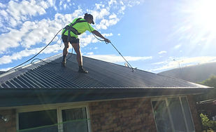Roof painting denim blue with airless sprayer and safety harness equipment