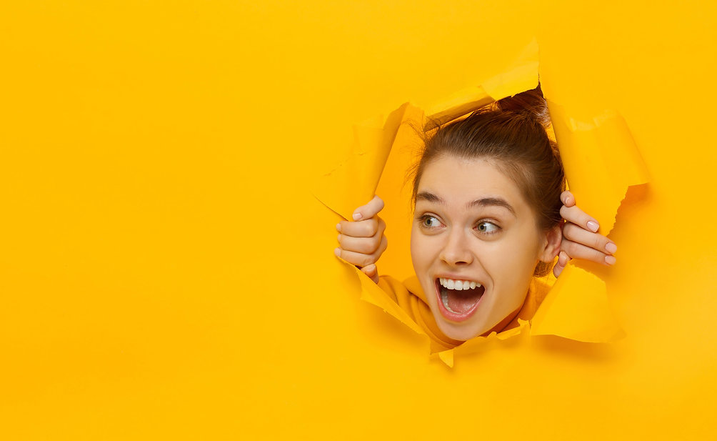 Excited young woman looking through hole