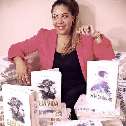 A autora Dani Assis entre os livos Sem Vida e Sem Caminho.