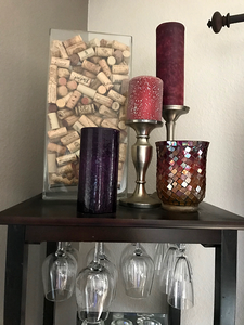 Red and purple candles, a mosaic candle holder, and a rectangular glass vase filled with wine cork on top of a wine rack holding wine glasses