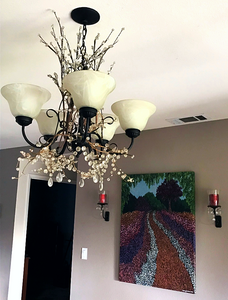 Colorful garden painting on wall and chandelier with twigs and crystals that were also used to make crystal jewelry