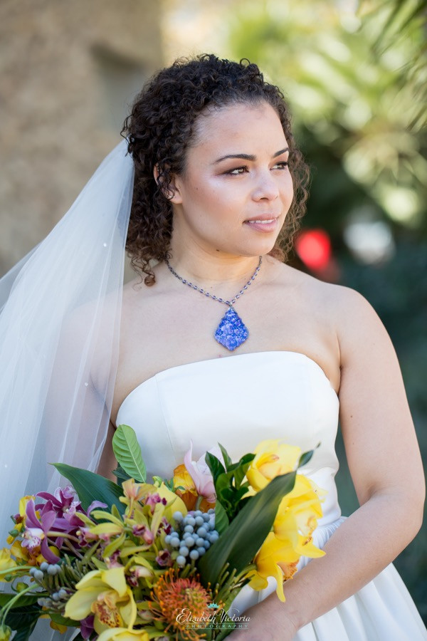 Woman wearing a crystal statement necklace necklace in an outdoor wedding dress holding a colorful floral bouquet at a boho wedding