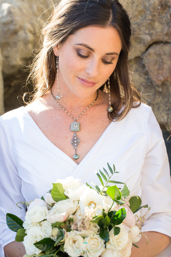Woman wearing a boho necklace, long earrings, and an outdoor wedding dress holding a white floral bouquet at a boho wedding on the beach