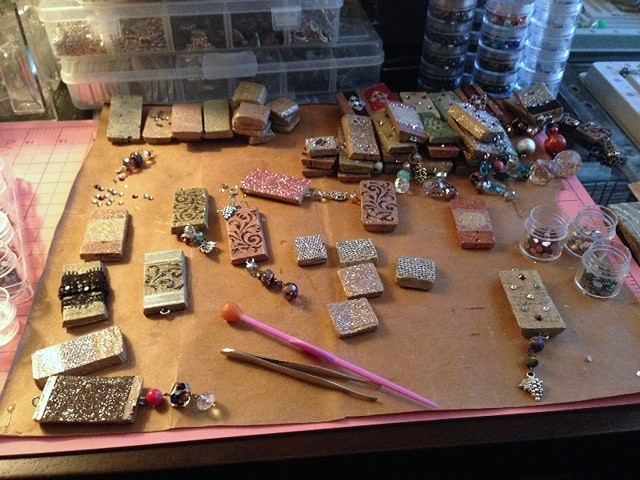 In the studio of a jewelry designer, image of wine corks necklaces in progress with jewelry designer tools on a work table