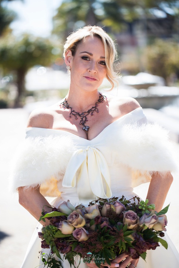 Woman wearing a crystal statement necklace and boho wedding dress holding a mauve floral bouquet at a boho wedding