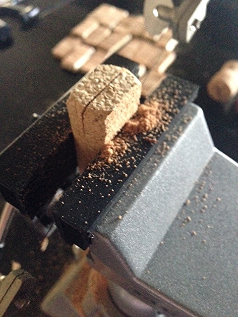 In the studio of a jewelry designer, image of a wine cork being cut in a vise