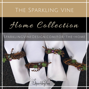 Wine lovers' gifts with text that reads introducing the home collection & an image of white napkins & napkin rings made of grapevines, crystals, & fabric leaves