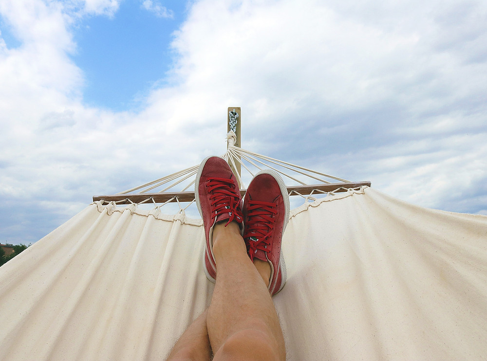Person lying down in a hammock in first person perspective looking at the sky. Image used on a personal injury lawyer blog