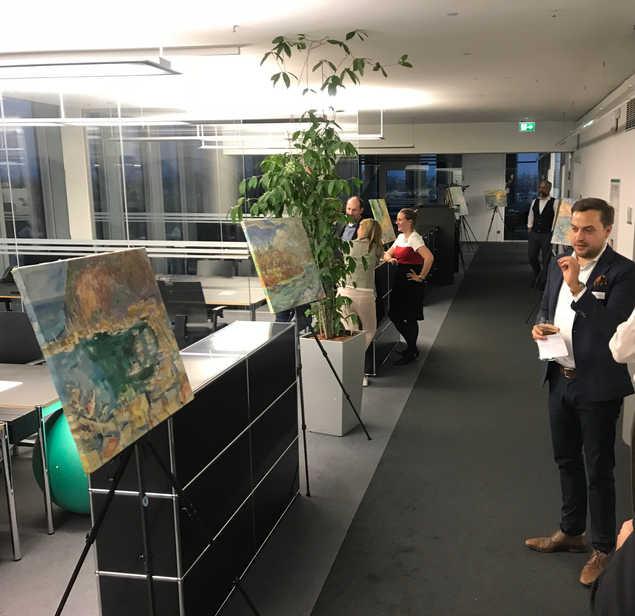 Nikolas erklärt die Geschichte der Gemälde bei einer Vernissage in den Münchner High Light Towers im Jahr 2018.  Nikolas explaining the story of the paintings at a Vernissage in Munich's High Light Towers in 2018.