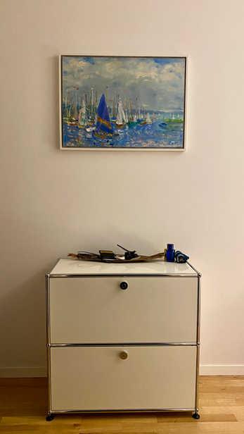 "Evas ""Segeltag am Ammersee"" durch den weißen Rahmen wundervoll kombiniert mit moderner Einrichtung.  Eva's scene of sailing boats on Lake Ammersee nicely combined – through the white frame –  with modern furniture."