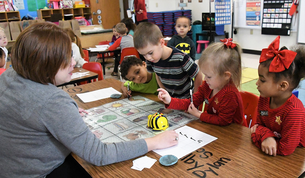 "Davina Mason, early childhood teacher at Lamar Elementary, offers encouragement and assistance as students work to code and program their Bee Bot to travel a prescribed route. ""One of the significant advantages of this program is that it teaches our students to think through, plan, and work through a ""problem"" when it doesn't turn out just right,"" said Mason. ""They have to figure out why it didn't come together as it should…and try again. It teaches the soft skill of perseverance."""