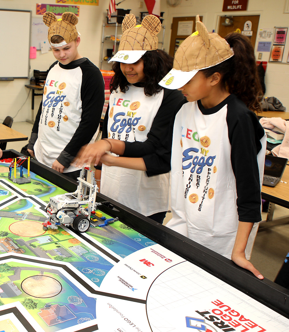 Three BMAC students program the LEGO robot