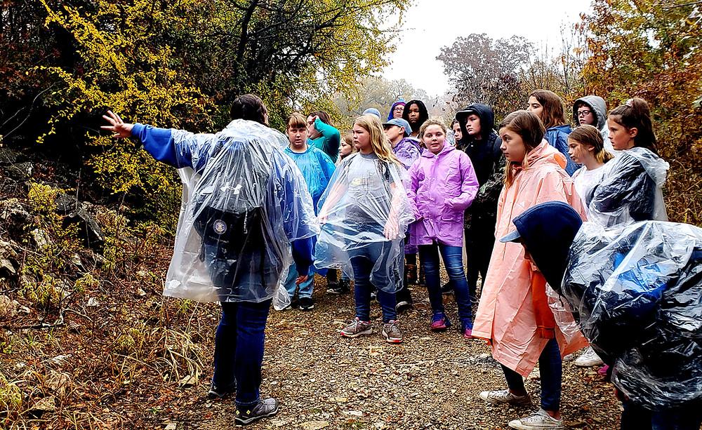B. McDaniel campers hike the trail in the rain