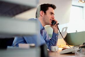 man_on_desk_phone_in_office.jpg