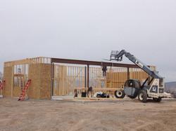 Steel beam being set on large shop