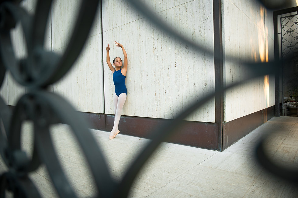 Level 3 ISB dancer leaning against a wall, posing with arms in 5th position and legs in sous-sus.