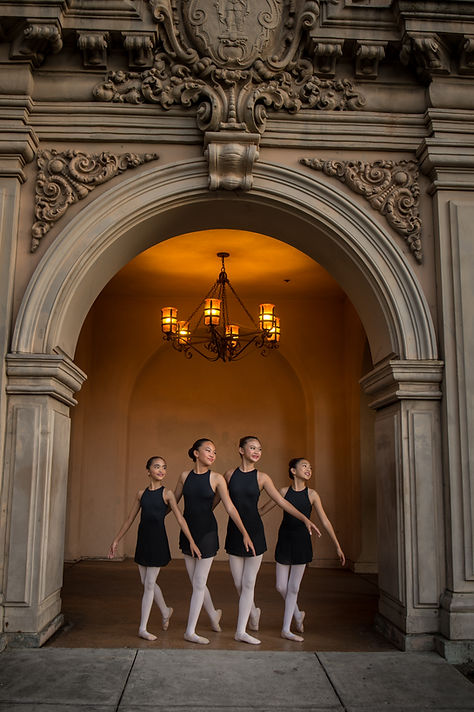 Four ISB ballet dancers posed under an archway at Balboa Park in San Diego, CA. Dancers are posing in B+ position.