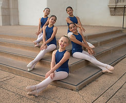 Five ISB ballet dancers seated by the stairs at Balboa Park in San Diego, CA.
