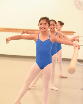 Young ISB ballet dancers posing for a photo near the barre. Dancers are holding the barre with their left hand, have their right arm in second position, and the right leg exteded in a tendu to the side.