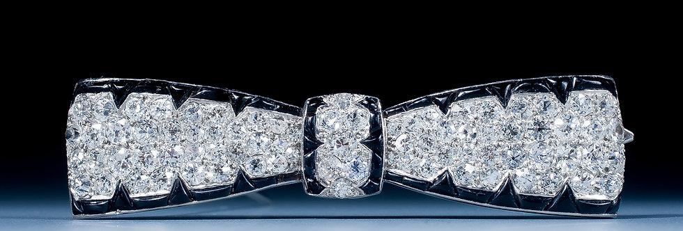 An Art Deco onyx and diamond brooch
