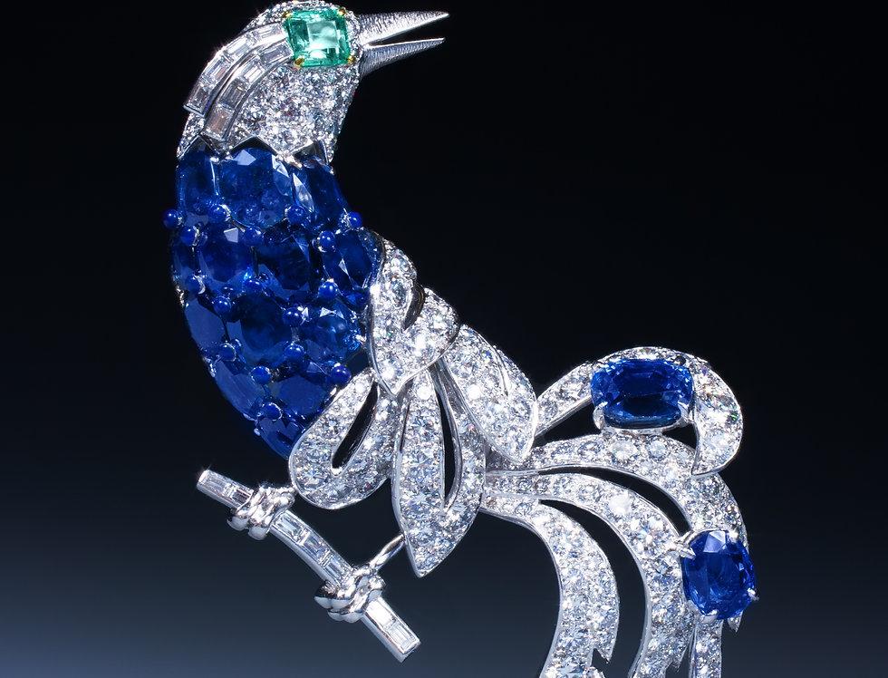 An impressive sapphire, emerald and diamond bird brooch by Cartier