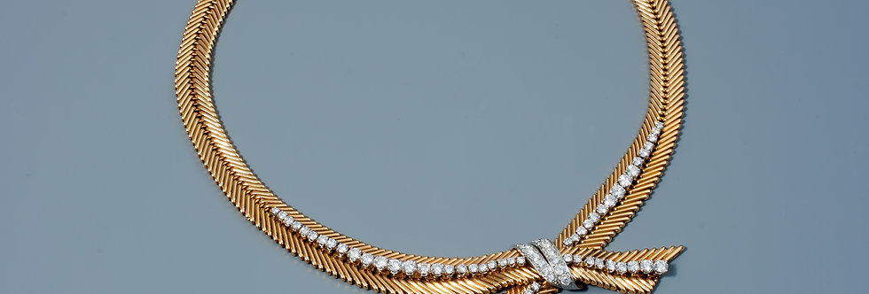 An elegant gold and diamond necklace of fishbone design by Van Cleef & Arpels