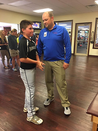 Dr. Travis Tarr helping young Athlete