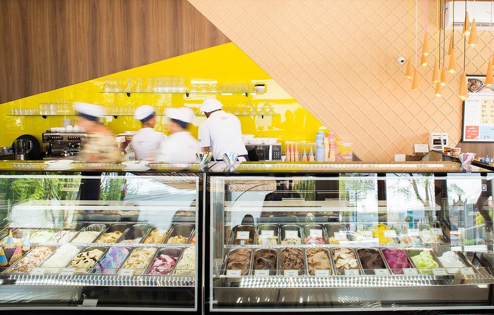 A imagem mostra uma foto interna da loja com a vitrine de sorvetes em primeiro plano
