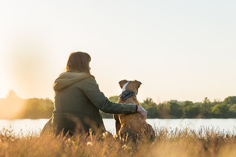 Dog owner and her pet sit at riverbank a
