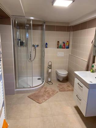 Koupelna v rodinném domě ve světlém obkladu.