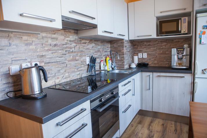 Kuchyňská linka, dvířka odstín Pinie, pracovní deska v barvě Mocca. A zádová deska s dekorem přírodního kamene.
