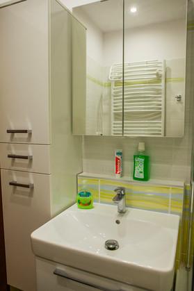Koupelna s obkladem zelená Samba. Vysoká skříň Interdoor.