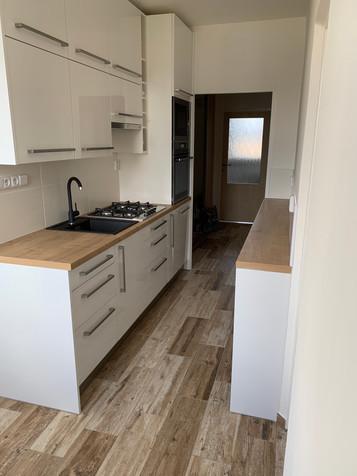 Kuchyňská linka v bílém akrylátovém lesku v kombinaci pracovní desky s odstínem dub Hamilton. Na pravé straně byly přidány skříňky a maximálně se tak využil volný prostor.