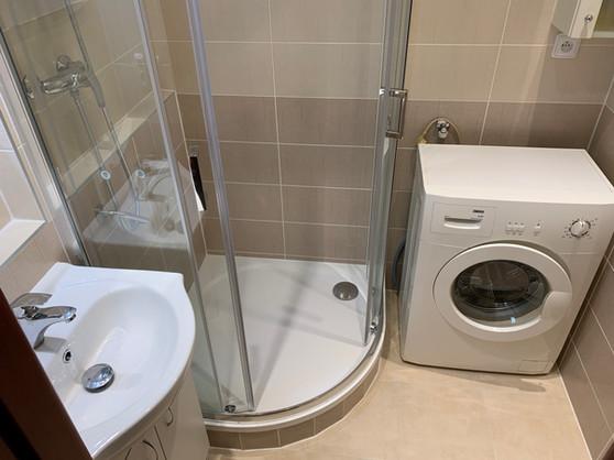 Obklady Textile v béžovém odstínu. Sprchový kout s bezpečnostním madlem.