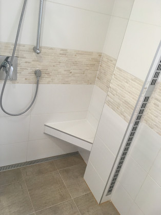 Sprchový kout se zděným sedátkem. Bílý obklad v kombinaci s přírodním kamenem.