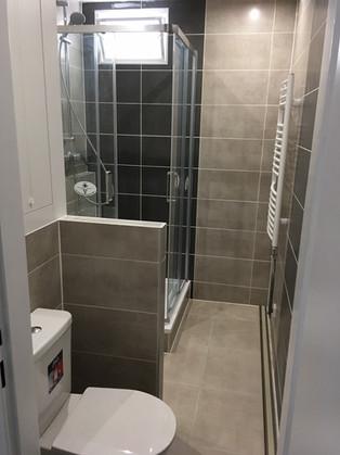 Koupelna v rodinném domě. Obklad imitace betonu až do stropu. Oddělený WC soklíkem dodá pocit soukromí i v menších koupelnách.