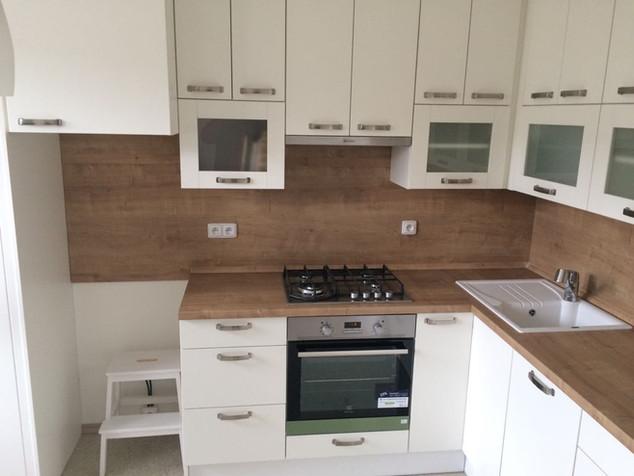 Bílá kuchyňská linka se zádovým panelem v barvě pracovní desky. Horní skříňky až do stropu s HKS výklopy na spodních prosklených dvířkách..