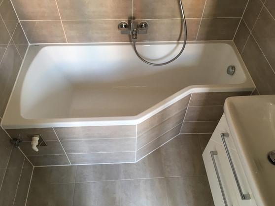 Koupelna ve světlém obkladu. Tvarovaná vana do malých prostor BeHappy od Ravak.