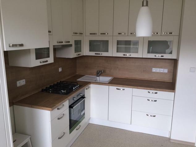 Bílá kuchyňská linka se zádovým panelem v barvě pracovní desky. Horní skříňky až do stropu s HKS výklopy na spodních prosklených dvířkách.