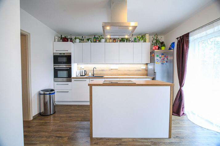 Kuchyňská linka s ostrůvkem v rodinném domě. Dvířka alpská bílá, pracovní a zádová deska dub Sherman koňakově hnědý, ostrůvková digestoř.