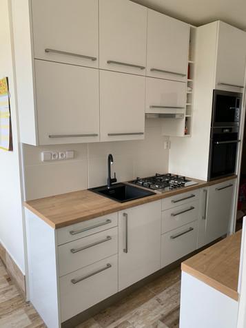 Kuchyňská linka v bílém akrylátovém lesku v kombinaci pracovní desky s odstínem dub Hamilton.