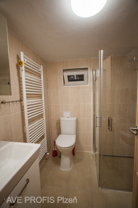 Koupelna v rodinném domě s béžovým obkladem Lazio a dlažbou Prato. Bezbariérový přístup do sprchového koutu.