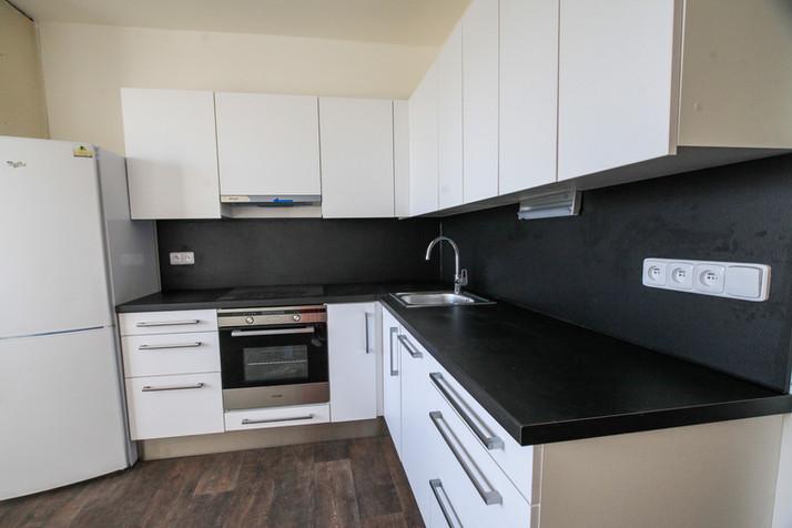 Kuchyňská linka Egger, dvířka jsou v barvě alpská bílá, černá pracovní i zádová deska, horní skříňky jsou bezúchytkové.