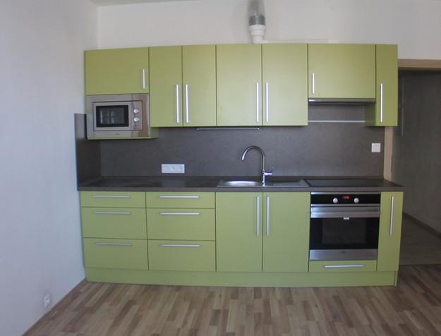 Zelená kuchyně v kombinaci s šedivou zádovou a pracovní deskou.