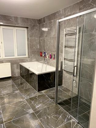 Koupelna s obkladem imitace přírodní mramor.