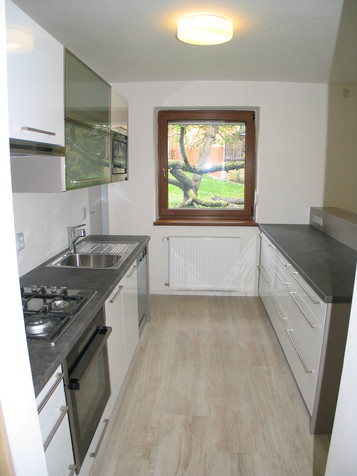 Kuchyňská linka s ostrůvkem v bílém lesku v kombinaci šedého betonu. Výklopy na horních skříňkách pro pohodlné otevírání skříněk.