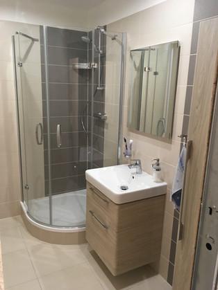 Koupelna v teplém odstínu se skříňkami ve dřevě.