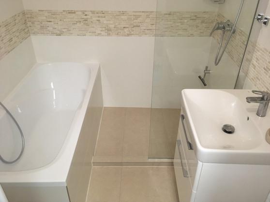 Koupelna s vanou i s vyzděným sprchovým koutem. Obklad mozaika z přírodního kamene v kombinaci se světlým obkladem.