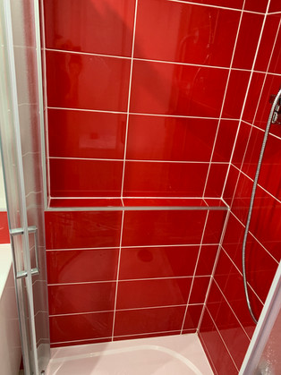 Netradiční koupelna s obkladem Joy červená. Sprchový kout s vyzděným odkládacím prostorem.